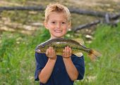pic of bluegill  - Happy child with a big fish he caught next to a pond - Largemouth Bass