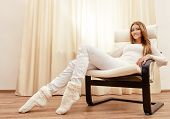 Happy young woman resting at home in a comfortable chair.
