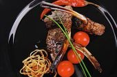 ribs on black with pepper and cherry tomatoes
