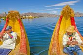PUNO, PERU, MAY 5, 2014:  Local men, Inhabitants of Uros Islands (Lake Titicaca), row the traditional reed boat