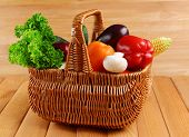 Fresh organic vegetables in wicker basket on wooden background