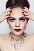 Portrait of young beautiful woman with stylish make-up and manicure