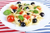 Spaghetti with tomatoes, olives and basil leaves on plate on napkin
