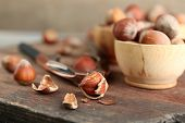 Hazelnuts in wooden bowls, on napkin on wooden background