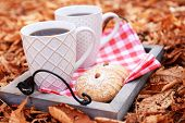 Cups of tasty hot drink and fresh cookies on tray, on autumn leaves background