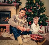 Young father with his son near fireplace in Christmas decorated house interior