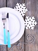 White plates, fork, knife and Christmas tree decoration on wooden background