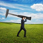 angry young businessman holding hammer and screaming at outdoor