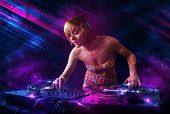 Beautiful young Dj playing on turntables with color effects