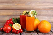 Carrot and tomato juice in glasses and fresh vegetables on wooden table on wooden wall background