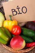 Basket of organic vegetables on wooden background