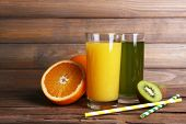 Orange and kiwi juice and fresh fruits on wooden table on wooden wall background