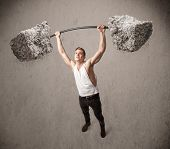 Strong muscular man lifting large rock stone weights