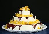 Beautiful wedding cake with oranges and chocolate on dark background