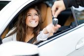 stock photo of key  - Young woman receiving the keys of her new car - JPG