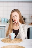 Young blonde woman drinking coffee
