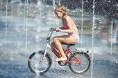 Little Girl Rides His Bike Among Fountains
