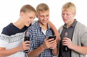 Smiling young guys drink beverages and use the smartphone. Two of the boys twin brothers.