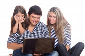 Happy family sitting on the carpet and using a notebook