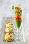 festive appetizers with avocado puree, red caviar and cucumber sandwiches