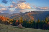 Autumn landscape. Mountain meadow with haystack. Beautiful clouds at sunset. Carpathians, Ukraine, Europe