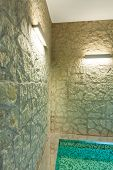 modern hotel spa interior, hot tub, stone wall