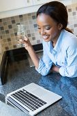 smiling black woman with glass of water using laptop in the kitchen at home