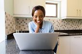cheerful african woman browsing internet on laptop