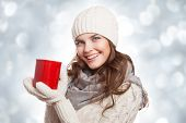 Beautiful smiling woman with a cup of coffee on the winter background.