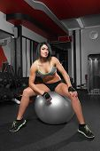 Athletic Woman Sitting On A Gym Ball