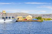 PUNO, PERU, MAY 5, 2014:  Inhabitants of Uros Islands welcome tourists arriving by boat