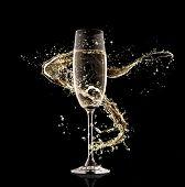 Celebration theme. Glass of champagne with splash, isolated on black background