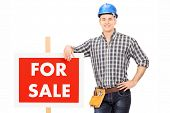 Male repairman leaning on a for sale sign isolated on white background
