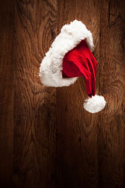 image of x-max  - Vertical shot of a Santa hat hanging on a wooden surface  - JPG