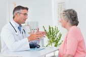foto of conversation  - Side view of male doctor conversing with female patient at table in clinic - JPG