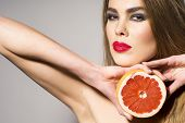picture of pomelo  - Young woman holding grapefruit cut in half next to the head healthy life concept photoset of attractive girl holding a cut piece of pomelo in her hands - JPG