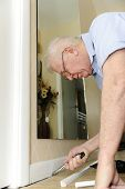 picture of baseboard  - A senior man pulling nails from his baseboard as he upgrades his home - JPG