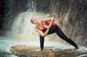 stock photo of revolver  - Woman practicing yoga near waterfall - JPG
