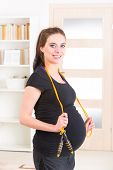 foto of jump rope  - Young pregnant woman exercising with skipping rope or jump rope at home - JPG