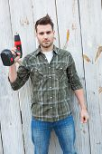 stock photo of hand drill  - Portrait of confident carpenter holding hand drill outside wooden cabin - JPG