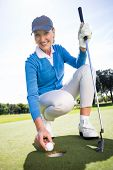 picture of ladies golf  - Smiling lady golfer kneeling on the putting green on a sunny day at the golf course - JPG