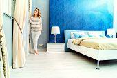 pic of model home  - Happy elegant woman having a rest in her bedroom - JPG