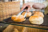 stock photo of tong  - Hand of server taking bread with tongs at the bakery - JPG