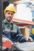 picture of forklift driver  - Portrait of driver operating forklift machine in warehouse - JPG