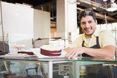 picture of red velvet cake  - Smiling worker showing red velvet at the bakery - JPG