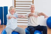 stock photo of senior class  - Portrait of senior couple with arms raised sitting on exercise ball at gym - JPG