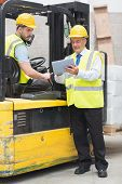 stock photo of forklift driver  - Forklift driver talking with his manager in a large warehouse - JPG