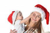 image of santa baby  - Cheerful baby girl and woman in Santa Claus hat - JPG