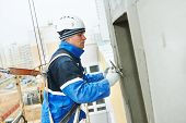 picture of putty  - builder at facade plastering work during industrial building with putty knife float - JPG