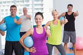 pic of senior class  - Portrait of happy female instructor with class holding medicine balls while gesturing thumbs up at gym - JPG